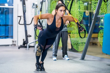 Girl doing exercises with trx at gym push ups Concept sport workout fitness healthy lifestyle.