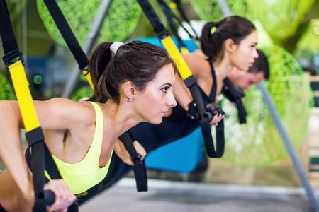As pessoas no ginásio fazendo exercícios elástica corda Conceito desporto treino de fitness estilo de vida saudável. Imagens - 48201699