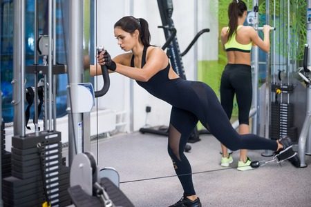 out of body: Woman exercising with crossover in fitness club or gym training legs, buttocks.