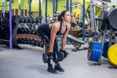 Fit woman fitness performing doing deadlift exercise with dumbbell Imagens