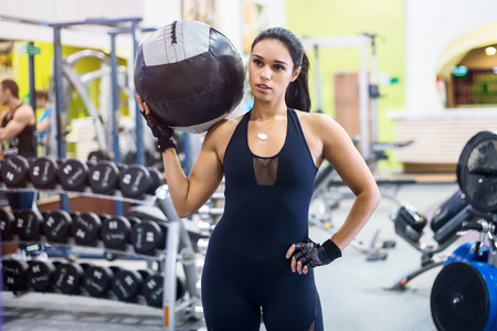 med: Muscular fit woman workout in gym. Strong female doing exercise with medicine ball in fitness club
