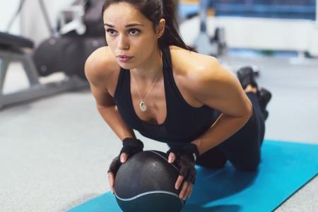 Mulher apta que exercita com treino bola de medicina fora de armas tr�ceps treinamento f�sico e b�ceps fazendo flex�es. Imagens - 48212927