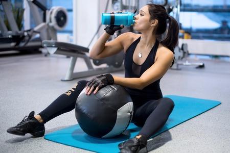 sediento: aptitud atleta mujer de agua potable después del entrenamiento de trabajo a cabo el ejercicio. Foto de archivo