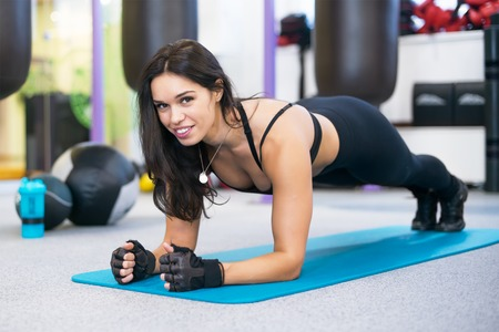 doing: training fitness woman doing plank core exercise working out for back spine and posture Concept pilates sport