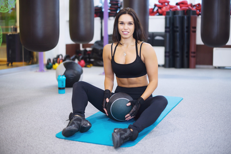 smilling: Work out fitness woman exercising with medecine ball in gym smilling and looking at camera Stock Photo