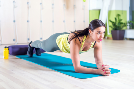 fitness training atletische sportieve vrouw doet plank oefening in de sportschool of yogales begrip te oefenen workout aërobe.