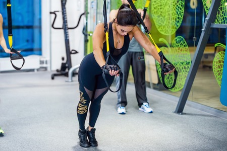 Young woman training exercise push ups with trx fitness straps in the gym  Concept sport workout healthy lifestyle.
