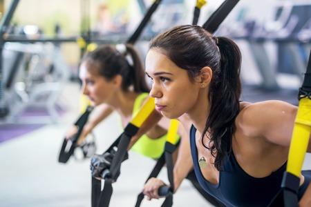 gimnasio mujeres: Gimnasio trx entrenamiento correas de suspensión ejerce la mujer haciendo flexiones, trabajando con el propio weith en el gimnasio Foto de archivo