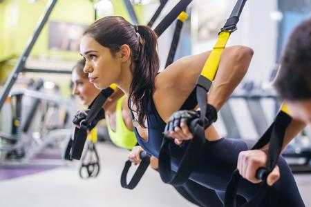 체육관 개념 운동 건강한 라이프 스타일 스포츠에서 푸시 업을 TRX 피트니스 스트랩과 훈련 팔을하는 여성 스톡 콘텐츠