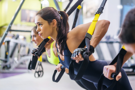 gordos: Mujeres que hacen flexiones brazos de capacitación con correas de fitness TRX en el deporte estilo de vida saludable ejercicio Concepto gimnasio Foto de archivo