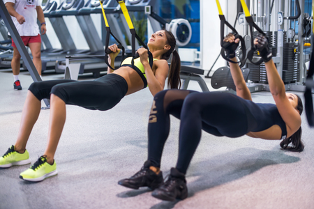 Woman exercising with suspension straps in fitness club or gym Imagens