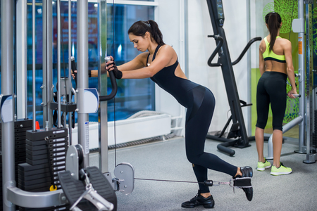 Woman exercising with crossover in fitness club or gym training legs, buttocks. photo