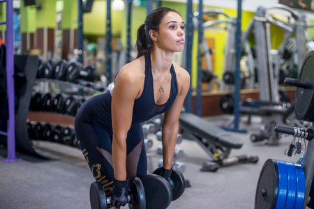 pesas: Ajuste aptitud Mujer que realiza haciendo ejercicio de peso muerto con mancuernas