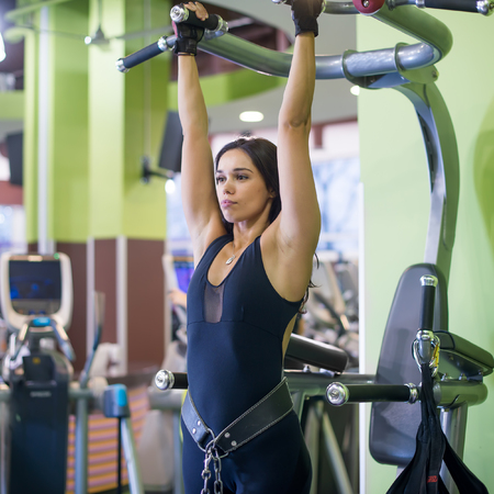 grapple: Woman performing pull ups in a bar at gym Stock Photo