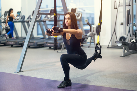 lunges: Athletic woman workout out squats weighted lunges exercise for butt legs with suspension straps in fitness club or gym