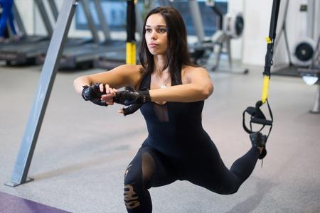 adentro y afuera: Entrenamiento de la mujer atlética a cabo sentadillas estocadas ponderados de ejercicio para las piernas a tope con las correas de suspensión en el gimnasio o en el gimnasio