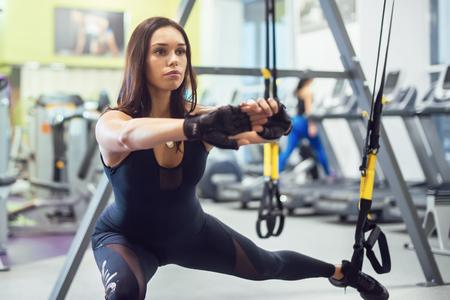 フィットネス クラブやジムの懸濁液のストラップでお尻脚の加重スクワット突進運動を運動の女性運動