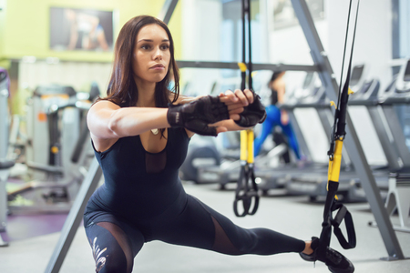 Athletic woman workout out squats weighted lunges exercise for butt legs with suspension straps in fitness club or gym
