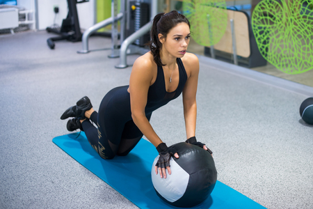 woman chest: Fit woman exercising with medicine ball workout out arms Exercise training triceps and biceps doing push ups.