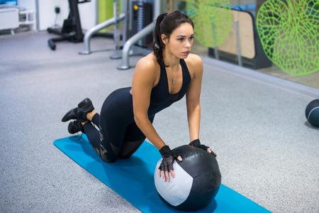 capacitaci�n: Mujer apta que ejercita con ejercicios de bal�n medicinal armas fuera tr�ceps y b�ceps haciendo flexiones de entrenamiento de ejercicios. Foto de archivo