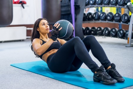 hands on stomach: Work out fitness woman doing sit ups abs abdominal crunches core exercises with medecine ball