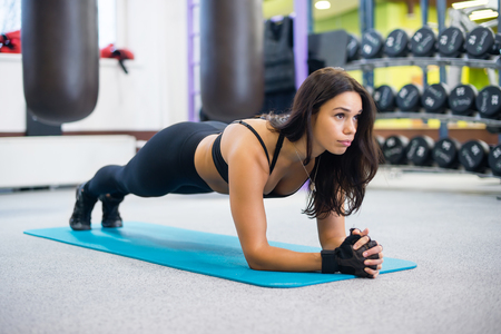 portrait fitness training athletic sporty woman doing plank exercise in gym or yoga class concept exercising workout aerobic.