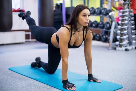 athletic sporty slim woman doing yoga exercise in the gym balancing outstretched on one knee. Fitness, sport, training. Stock Photo