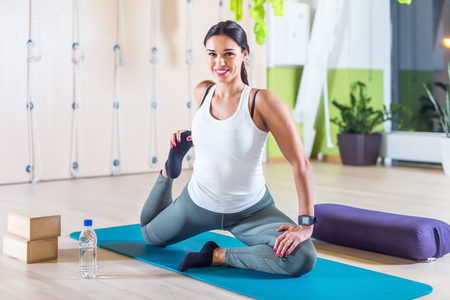 woman stretching: Fit woman doing stretching pilates exercises in fitness studio