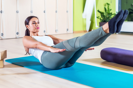 woman laying: Fit woman stretching at yoga class in fitness studio doing exercise abdominal crunches in the gym