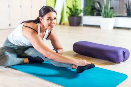 WOMAN FITNESS: Fit woman doing stretching pilates exercises in fitness studio
