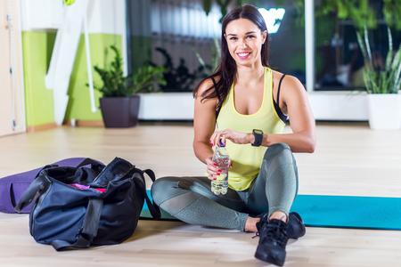 Mulher da aptidão do atleta de água potável após o trabalho de formação para o exercício. Imagens