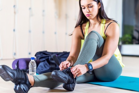 Fit sporty young woman lacing trainers shoes at fitness club 스톡 콘텐츠