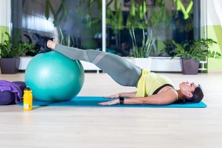 ejercicio aeróbico: Vista lateral de la mujer que hace la mitad del puente presentan en estudio de la aptitud prácticas piltes o el yoga ejercicios de calentamiento para la columna vertebral, salto mortal hacia atrás, el fortalecimiento de músculos de la espalda.