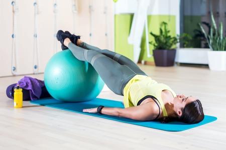 Vista lateral da mulher que faz meia ponte levantam no estúdio de fitness práticas piltes ou yoga exercícios de aquecimento para a coluna, backbend, fortalecendo os músculos das costas. Imagens