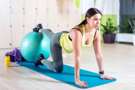 espina dorsal: Mujer que hace ejercicios de pilates con pelota en forma en el gimnasio o yoga clase
