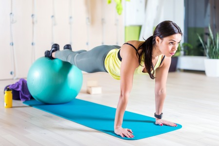 Woman doing pilates exercises with fit ball in gym or yoga class