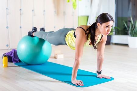 Mulher que faz exerc�cios de Pilates com esfera do ajuste na gin�stica ou ioga classe Imagens - 48565370