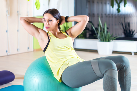 crunches: Fitness young woman doing abdominal crunches on fit ball