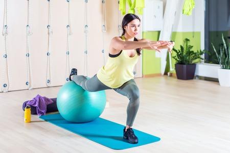 헬스 클럽이나 요가 클래스에 맞는 공을 가진 한쪽 다리를 쪼그리고 필라테스 운동을하는 여성
