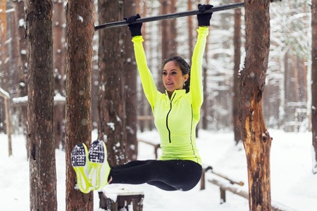 gripping bars: Fit girl training abs by raising legs on a horisontal bar. Fitness woman workout doing exercises outdoor winter park