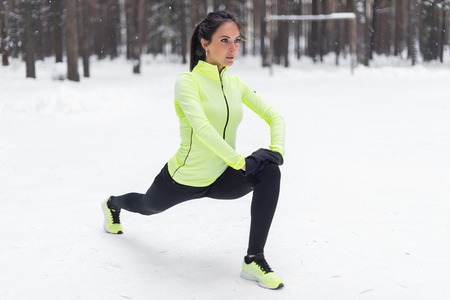 hamstring: Fit woman doing stretching exercises before running outdoors Winter street training Stock Photo
