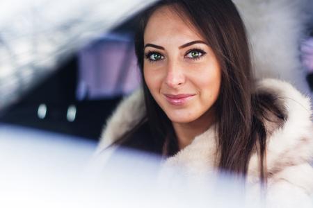 fur coat: Portrait of beautiful smilling woman car driver in fur coat