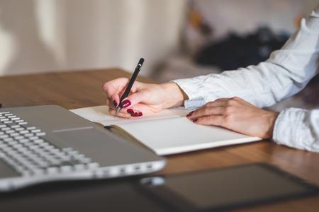 zakenvrouw met laptop en dagboek in kantoorconcept freelance werk thuis Stockfoto