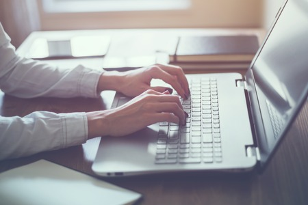 Woman working in home office hand on keyboard close up.