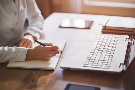 女性フリーランス女性手ペンとノートを自宅やオフィスに書いて