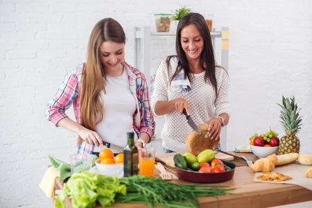 Prachtige jonge vrouw voorbereiding van het diner in een keuken-concept het koken, culinair, gezonde levensstijl Stockfoto