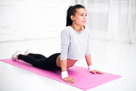 columna vertebral: Chica haciendo el calentamiento de ejercicios para la columna vertebral, salto mortal hacia atrás, arqueando su espalda estirar ejercicio en casa o clase de yoga. Foto de archivo