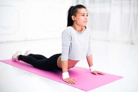 spine: Girl doing warming up exercise for spine, backbend, arching stretching her back  working out at home or yoga class. Stock Photo