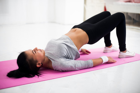 positions: Bridge pose sporty woman doing warming up exercise for spine, backbend, arching stretching her back  working out at home fitness workout yoga gymnastics concept. Stock Photo