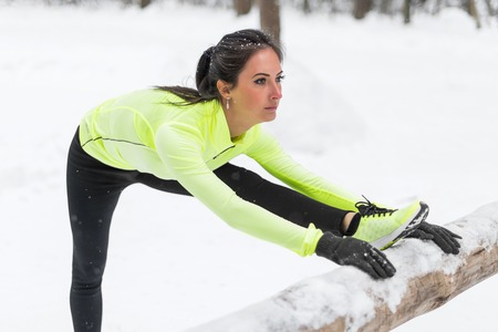 hamstrings: Fitness model athlete warm up stretching her hamstrings, leg and back. Young woman exercising outdoors winter in park